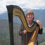 Barbara playing harp wedding music in Vail, Colorado on the top of a mountain.